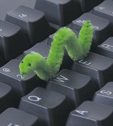 Un gusano de peluche sobre un teclado de ordenador. Virus.
